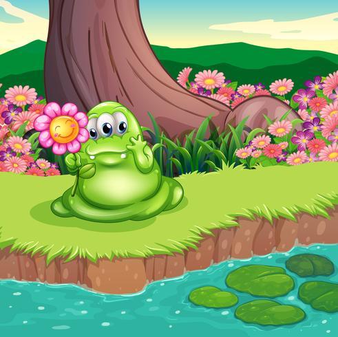 Un monstre vert au bord de l'eau tenant une fleur vecteur