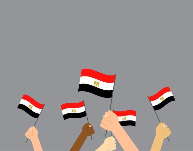 Mains d'illustration vectorielle tenant des drapeaux de l'Égypte sur fond gris vecteur