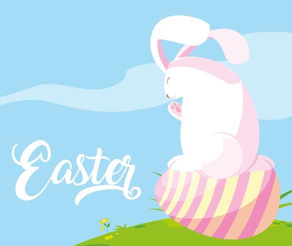 mignon lapin avec oeuf de Pâques dans l'herbe vecteur