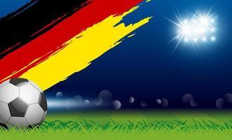 ballon de football sur l'herbe et le coup de peinture du drapeau allemand