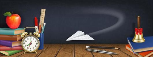 avion en papier volant devant le tableau et les fournitures