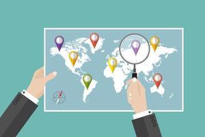 L'homme tient la carte du monde avec des épingles d'objectif de voyage