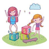 bonne journée des enfants, filles jouant avec des blocs et de l'herbe de skateboard