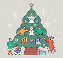 les gens décorent un énorme sapin de Noël.