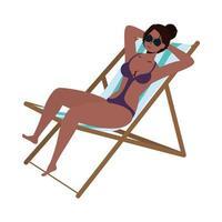 Belle femme noire en maillot de bain et assise dans une chaise de plage