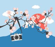 Appareil photo suspendu avec une branche florale rose au mont fuji