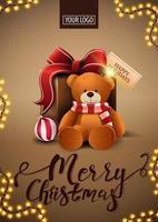 joyeux noël, carte postale verticale marron dans un style minimaliste avec cadre de guirlande et cadeau avec ours en peluche