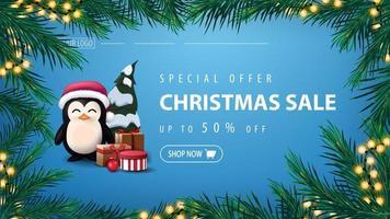 offre spéciale, vente de Noël, jusqu'à 50 rabais, bannière bleue avec guirlande de branches de pin avec guirlande jaune et pingouin en chapeau de père Noël avec des cadeaux