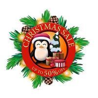 Vente de Noël, jusqu'à 50 de réduction, bannière de réduction ronde rouge avec des branches d'arbre de Noël, des cônes, des ampoules et un pingouin en chapeau de père Noël avec des cadeaux