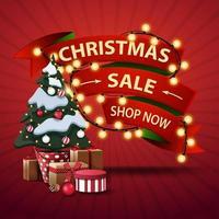 vente de noël, boutique maintenant, bannière de réduction sous forme de rubans enveloppés de guirlande et arbre de noël dans un pot avec des cadeaux vecteur