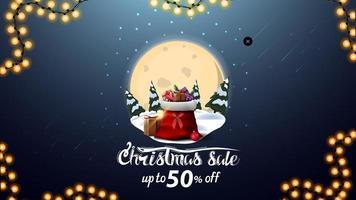 vente de Noël, jusqu'à 50 de réduction, bannière de réduction bleue avec grande pleine lune, congères de neige, pins, ciel étoilé et sac du père Noël avec des cadeaux vecteur