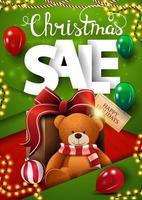 Vente de Noël, bannière de remise verte verticale dans un style de conception matérielle avec des ballons, des guirlandes et un cadeau avec ours en peluche
