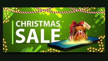 Bannière de réduction verte de Noël avec de grandes lettres, des guirlandes et un smartphone de l'écran qui semblent présents avec un ours en peluche