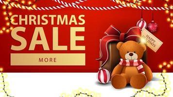 vente de noël, bannière de réduction rouge avec guirlandes, bouton et cadeau avec ours en peluche près du mur