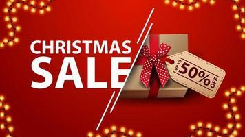 Vente de Noël, bannière de réduction rouge avec guirlande et cadeau avec noeud et étiquette de prix, vue de dessus vecteur