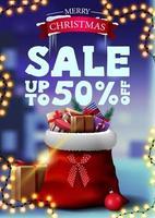 bannière de réduction de Noël avec guirlande et sac de père Noël avec des cadeaux. bannière de remise verticale avec paysage d'hiver flou sur le fond