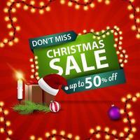 ne manquez pas, vente de Noël. Bannière de réduction rouge et verte avec cadeau avec chapeau de père Noël, bougies, branche d'arbre de Noël et boule de Noël
