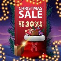 Vente de Noël, jusqu'à 30 rabais, bannière de réduction avec ruban vertical rouge décoré de branches d'arbres de Noël et sac de père Noël avec des cadeaux