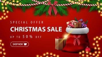 offre spéciale, vente de Noël, jusqu'à 50 rabais, belle bannière de réduction rouge avec des branches d'arbres de Noël, des guirlandes et un sac du père Noël avec des cadeaux