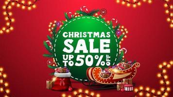 vente de Noël, jusqu'à 50 rabais, bannière de réduction rouge verticale avec cercle vert avec offre, décorée de branches d'arbres de Noël, de bonbons et de guirlandes et de traîneau du père noël et d'un sac avec des cadeaux