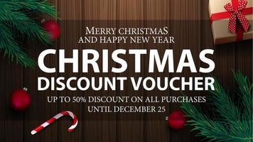 bon de Noël, jusqu'à 50 de réduction sur tous les achats. Bon de réduction de Noël avec présent, branches d'arbres de Noël, cannes de bonbon, boules de Noël et fond en bois, vue de dessus vecteur