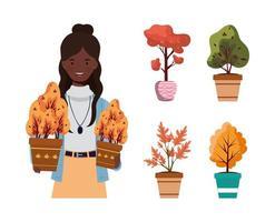 femme afro avec des plantes d'automne dans des pots en céramique vecteur