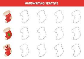 traçant des lignes avec des chaussettes de Noël de dessin animé. pratique des compétences d'écriture.