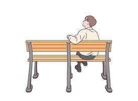 un homme est assis seul sur un banc. vecteur