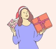 concept de Noël ou du nouvel an. jeune femme heureuse habillée en bonnet de Noel garde des boîtes avec des cadeaux de Noël. vecteur