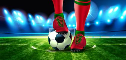 Ballon de foot sur le stade de football avec une partie du pied d'un joueur de football