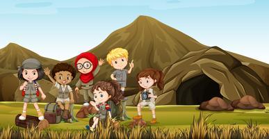 Enfants en costume de safari campant près de la grotte vecteur