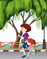 Papa et sa fille traversant un parc