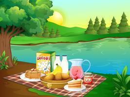 Petit déjeuner sur un tapis au bord de la rivière vecteur