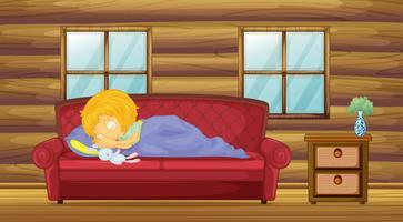 Une fille dort sur le canapé avec un jouet