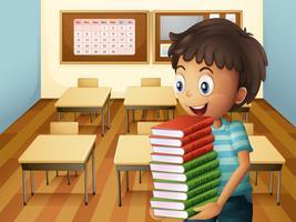 Un garçon portant une pile de livres