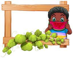 Un cadre en bois avec un garçon mangeant de la pastèque vecteur