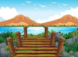 Scène de fond avec un pont en bois vers le lac