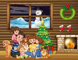 Famille assise devant l'arbre de Noël