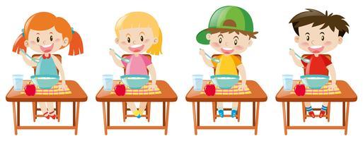 Quatre petits enfants prenant son petit déjeuner