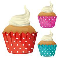 Cupcake à la crème dans des tasses de couleurs différentes vecteur