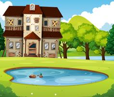 Vieille maison en brique avec pelouse et étang