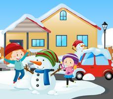 Deux filles et bonhomme de neige devant la maison