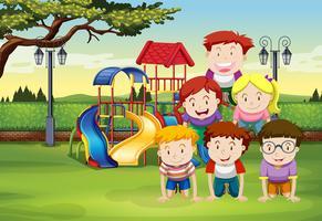 Enfants faisant la pyramide humaine sur l'herbe vecteur