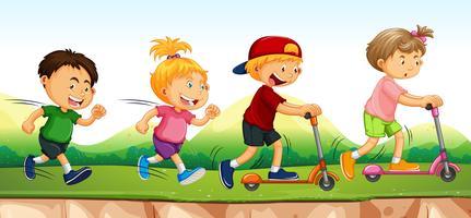 Quatre enfants courir et faire du scooter dans un parc