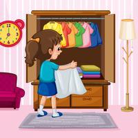 Une fille pliant le tissu dans la garde-robe vecteur