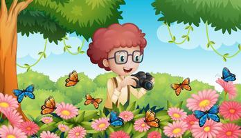 Garçon prenant une photo de papillons dans le jardin vecteur