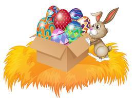 Un lapin poussant une boîte pleine d'oeufs de Pâques