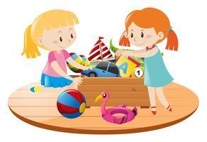 Filles et boîte pleine de jouets