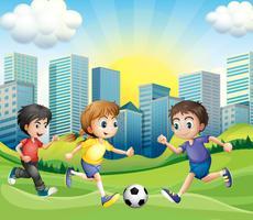 Enfants jouant au foot dans le parc vecteur