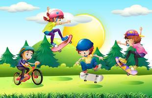 Enfants faire de la planche à roulettes et du vélo dans le parc